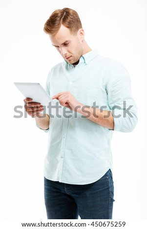 Portrait of a young redhead man using tablet computer isolated on a white background