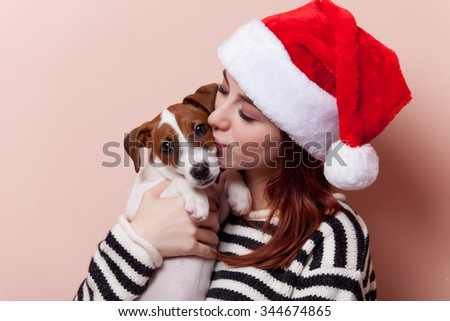 Portrait of a young redhead woman in Santa Claus hat with jack russell terrier puppy on pink background - stock photo