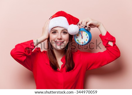 Portrait of a young redhead woman in Santa Claus hat with retro alarm clock on pink background
