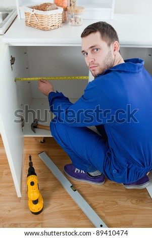 Portrait of a young repair man measuring something in a kitchen