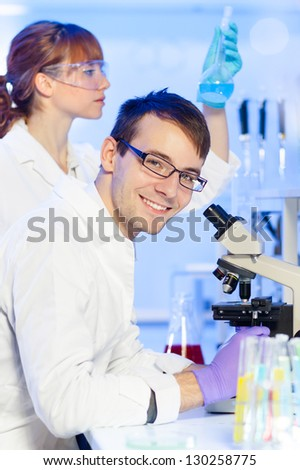 Portrait of a young researcher microscoping in the life science (forensics, microbiology, biochemistry, genetics, oncology.) laboratory. Assistant scientist examining blue liquid solution in the back. - stock photo