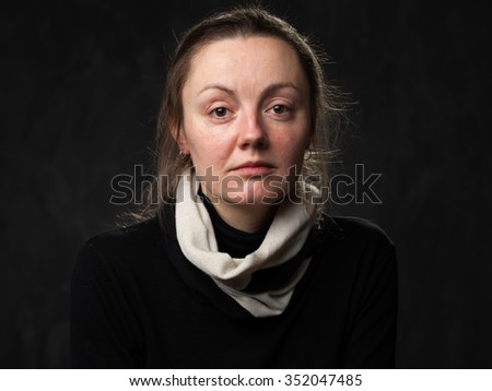 Portrait of a young sad disoriented woman in white scarf, gray background