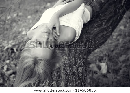 portrait of a young sad girl lying on a tree. Black and white. - stock photo