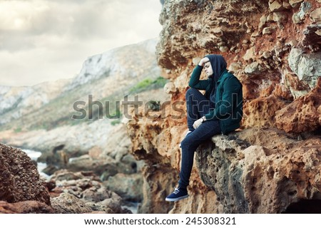 portrait of a young sad man sitting on the rocks. - stock photo