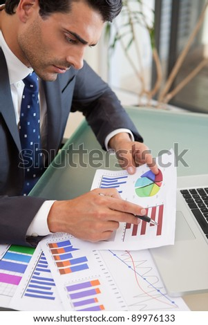 Portrait of a young sales person studying statistics in an office - stock photo