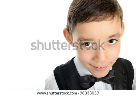portrait of a young school boy in black suit with deep brown eyes looking at camera isolated on white background - stock photo