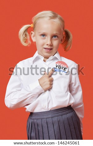 Portrait of a young school girl with vote badge over orange background - stock photo