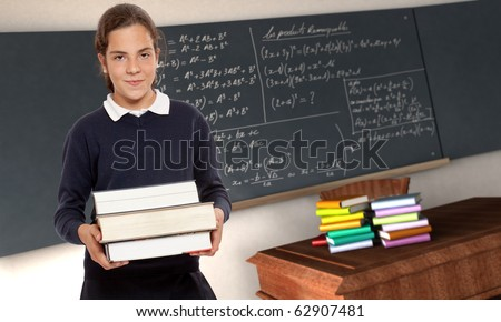 Portrait of a young schoolgirl holding heavy bookswith a blackboard with formulae as background
