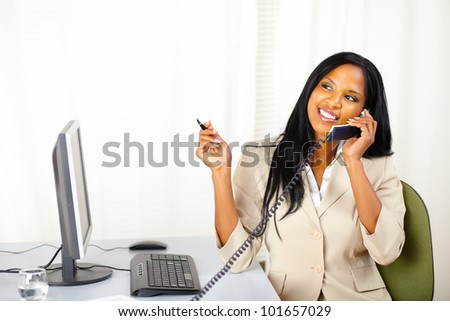 Portrait of a young secretary smiling while talking on phone and looking up - stock photo