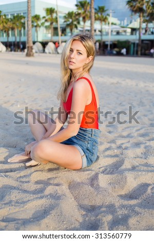 Portrait of a young seductive female model with a beautiful figure posing for the camera while sitting on the beach, charming blonde hair woman enjoying sunny afternoon during summer weekends