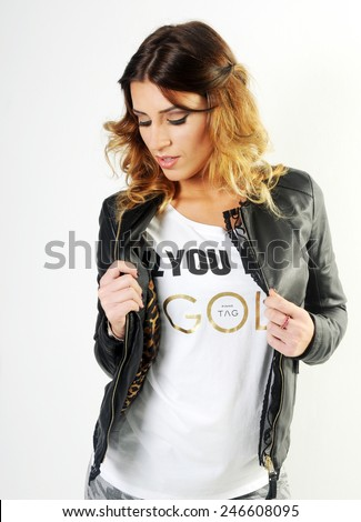 portrait of a Young sensual caucasian girl looking down and playing teasingly with her black leather jacket  - stock photo