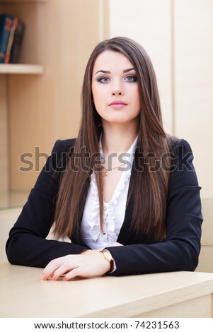 Portrait of a young serious businesswoman sitting near the table in office - stock photo