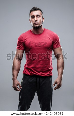 Portrait of a young serious man in red t-shirt over gray background - stock photo