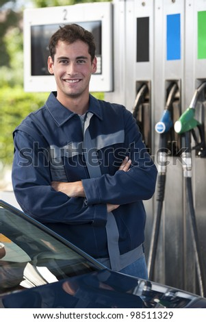 Portrait of a young service station worker smiling at camera - stock photo