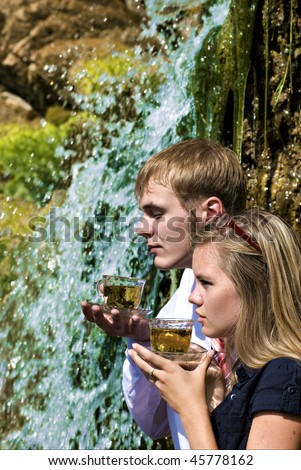 Portrait of a young sexy couple drinking a tea on waterfall