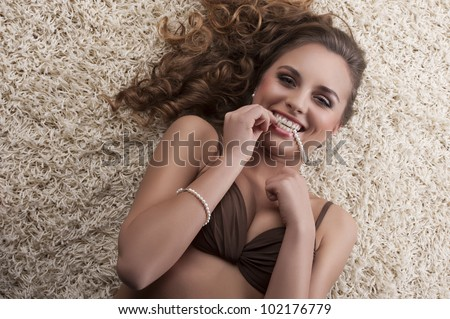 portrait of a young sexy girl in brown bra with a pearl necklace in her mouth laying on a white modern carpet - stock photo