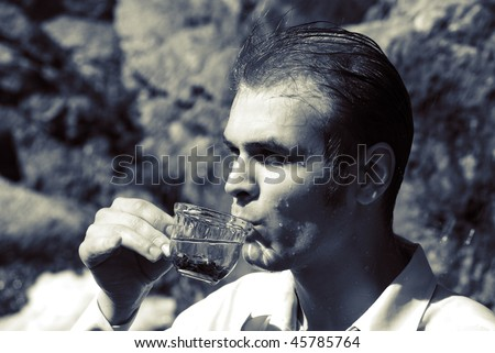 Portrait of a young sexy man drinking a tea on waterfall