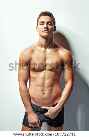 Portrait of a young sexy muscular man in underwear against white wall in sensual pose - stock photo