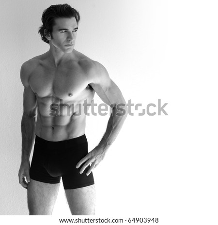 Portrait of a young sexy shirtless man in underwear against neutral background with lots of copy space - stock photo
