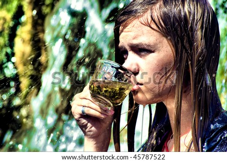 Portrait of a young sexy woman drinking a tea on waterfall - stock photo