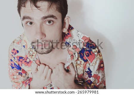 Portrait of a young shy man on a white background - stock photo