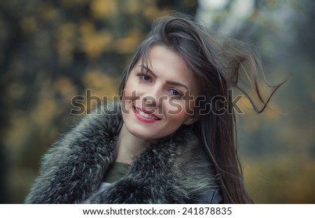 Portrait of a young smile woman wearing fur with a blurred nature background. Close up, head shot of cute girl, outdoors - stock photo