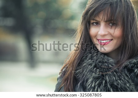 Portrait of a young smile woman wearing fur with a blurred nature background. Close up, head shot of cute girl, outdoors. Copyspace - stock photo