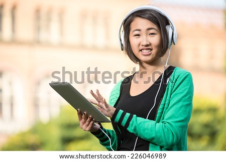 Portrait of a young smiling asian student with university building in the background. She is listening music with tablet. - stock photo