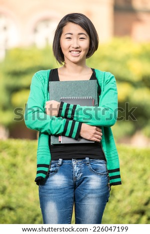 Portrait of a young, smiling, beautiful asian student with university building in the background. - stock photo