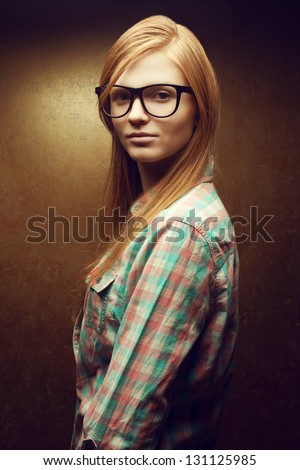 Portrait of a young smiling beautiful red-haired (ginger)  woman wearing trendy glasses and casual shirt. Girl  posing over golden background. Studio shot. - stock photo