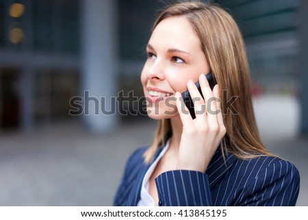Portrait of a young smiling business woman talking on her mobile phone in a business environment - stock photo