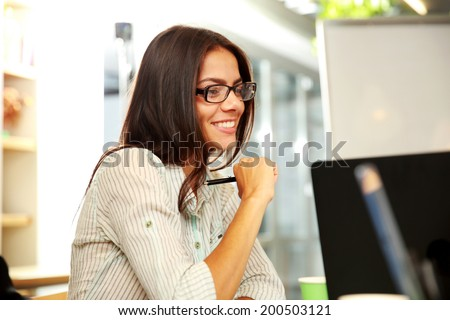 Portrait of a young smiling businesswoman in glasses at office - stock photo