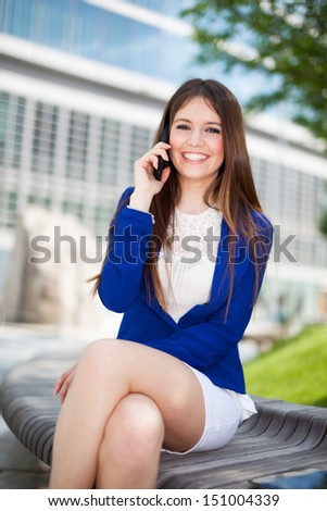 Portrait of a young smiling businesswoman talking on the phone