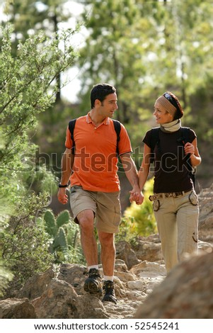 Portrait of a young smiling couple making some hike - stock photo