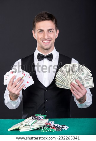 Portrait of a young smiling dealer with playing cards and money in hands. - stock photo