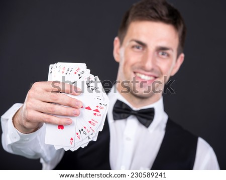 Portrait of a young smiling dealer with playing cards in his hands. - stock photo