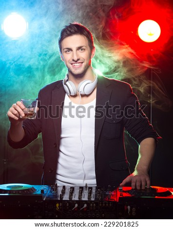 Portrait of a young smiling dj with mixer, on foggy background. - stock photo