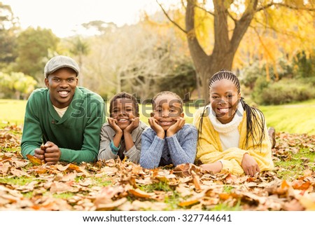 Portrait of a young smiling family lying in leaves on an autumns day - stock photo