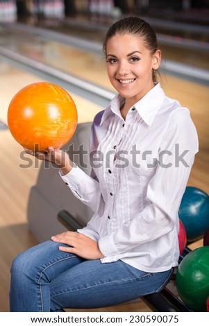 Portrait of a young smiling girl at the colored layers in bowling club.