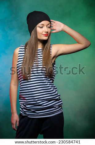 Portrait of a young smiling girl hip hop dancer, on the colored background. - stock photo