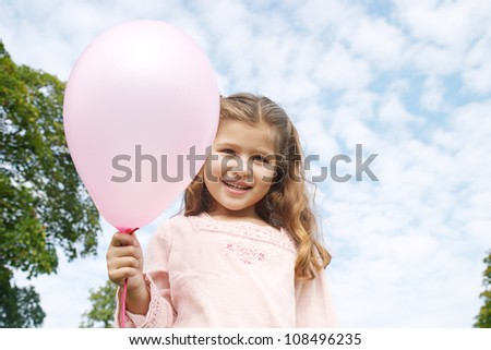 Portrait of a young smiling girl holding a pink balloon in the park on a sunny day. - stock photo