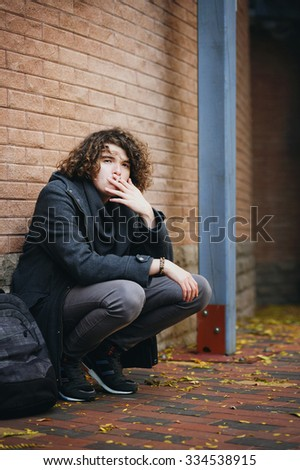 Portrait of a young smiling handsome man with curly hairstyle dressed in gray jacket, standing against brick wall and smoking a cigarette. - stock photo