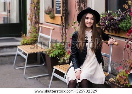 Portrait of a young smiling happy hipster girl sitting on a wooden chair near beautiful building with pots of flowers, cheerful gorgeous woman dressed in cool stylish clothes resting in urban setting - stock photo