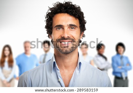 Portrait of a young smiling man in front of a group of people - stock photo