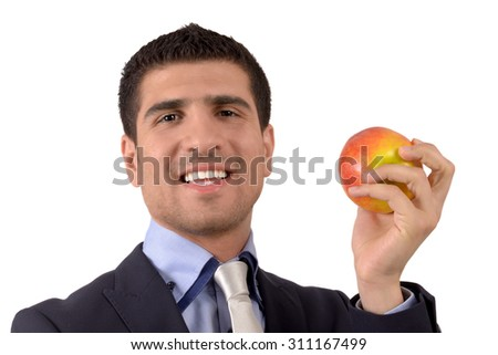 Portrait of a young smiling man in office suit holding a red apple in his hand isolated on white