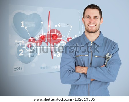 Portrait of a young smiling mechanic next to futuristic interface with diagram - stock photo