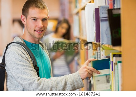 Portrait of a young smiling student selecting a book from bookshelf in the library