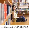 Portrait of a young smiling student using her laptop in a library - stock photo