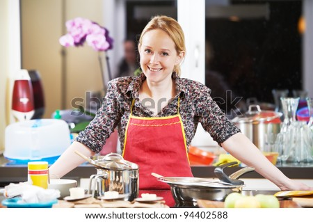 Portrait of a young smiling woman cooking in her kitchen - stock photo