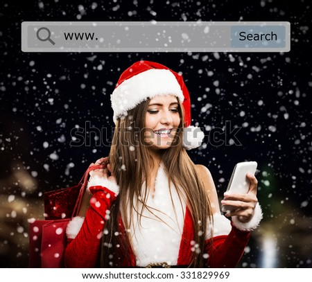 Portrait of a young smiling woman doing online shopping before christmas - stock photo